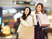 smiling young asian women carrying shopping bags.