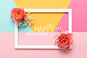 Happy Women's Day Pastel Colored Background. Flat lay greeting card with beautiful coral hue roses.