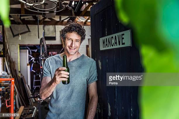 Heureux travailleur tenant la bouteille de bière dans l'atelier