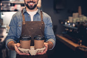 Outgoing bearded barista keeping mugs of liquid for client. Labor concept. Focus on coffee