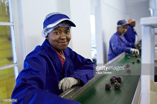 Happy worker sorting out figs on conveyer belt