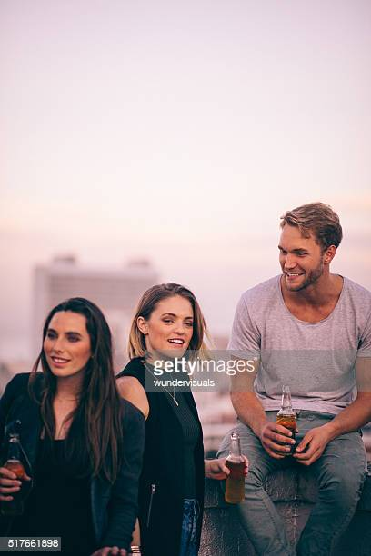 Happy young adult friends enjoying a rooftop party