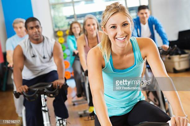 Happy young adult woman leading cycling fitness class