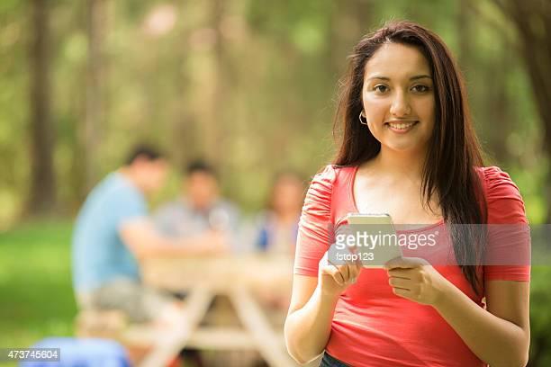 Felice giovane donna SMS su smart phone all'aperto.   Estate.