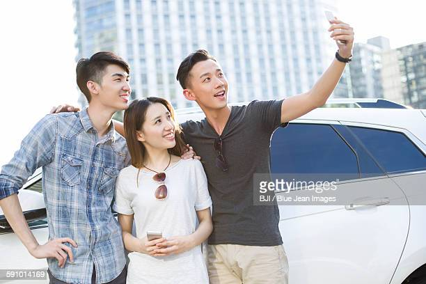 Happy young adults taking self portrait with a smart phone