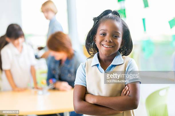 Happy young African American girl wearing private elementary school uniform