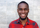 Close up portrait of happy young african man smiling against gray wall