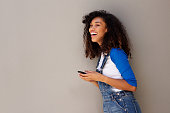 Side portrait of happy young african woman laughing with cellphone