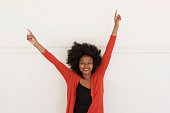 Portrait of happy young african woman with arms raised by white wall