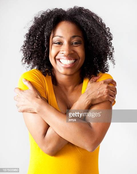 Glückliche junge afrikanische amerikanische Frau umarmen sich selbst