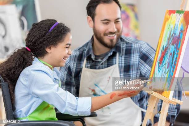 Happy young artist in wheelchair