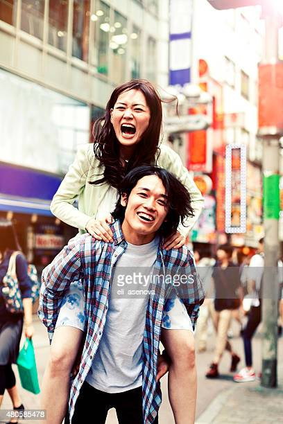 幸せな若いカップル、アジアの楽しいピギーバック