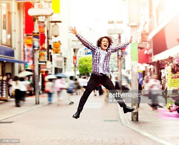 Happy young asian man jumping in Shibuya auf der Straße