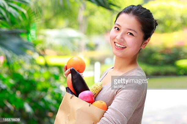 happy young asian woman holding vegetable and fruit