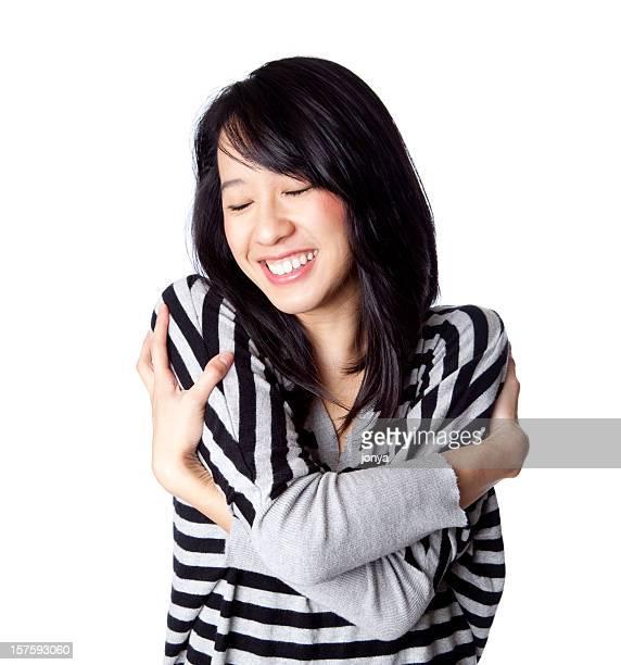 Glückliche junge asiatische Frau umarmen sich selbst