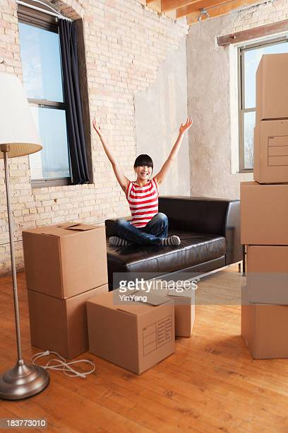 Happy Young Asian Woman Moving Boxes Into Loft Apartment Home