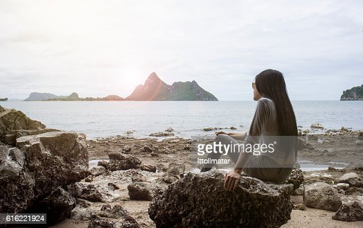 happy young asian woman sitting on a rock : Stock-Foto