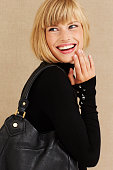 Happy young blond businesswoman laughing in studio