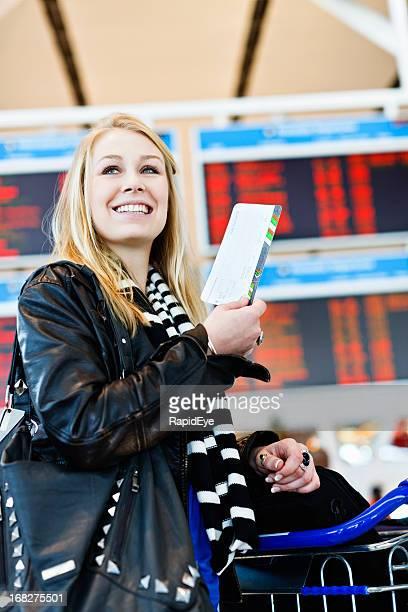 Heureux jeune blonde voyageurs avec carte d'embarquement à l'aéroport