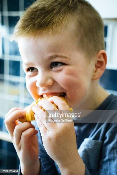 Heureux jeune garçon petit déjeuner, salle à manger Croissant