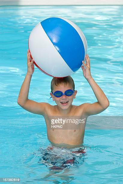 Heureux jeune garçon dans la piscine avec un ballon de plage