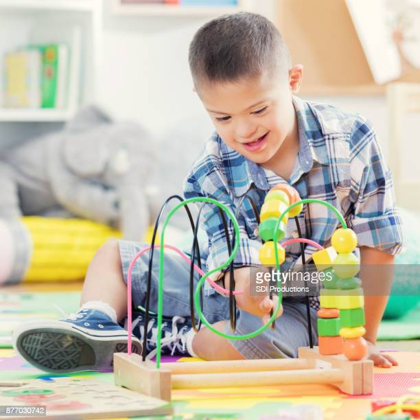 Happy young boy playing with bead rollercoaster in preschool class