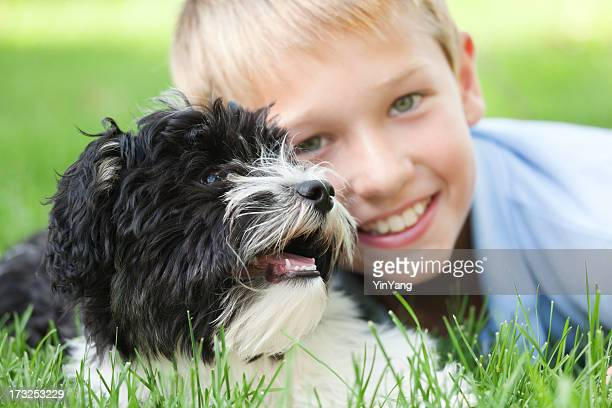 Happy Young Boy Playing with Family Pet Dog Close-up