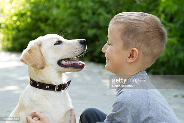 Happy young boy sitting with an excited dog with mouth open