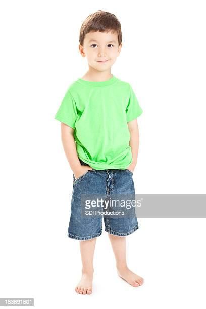 Happy Young Boy Standing With Hands in Pockets, White Background