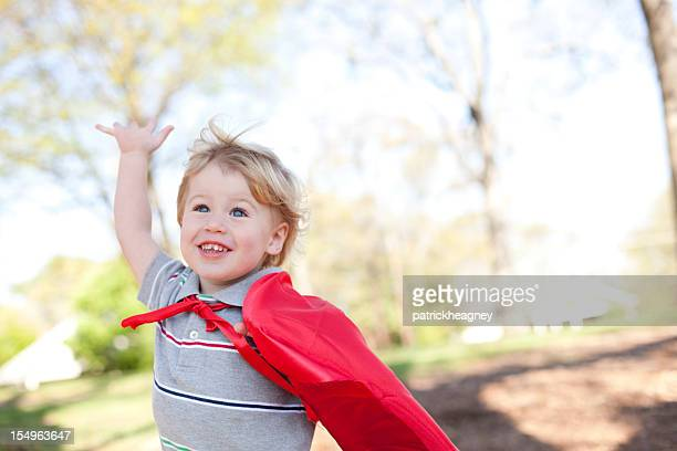Happy young boy wearing red cape