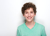 Close up portrait of a happy young boy with curly hair smiling against white background