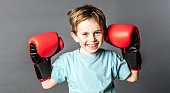happy young 6-year old boy with red hair and freckles smiling and holding his big boxing gloves up to win a sporty competition, grey background studio
