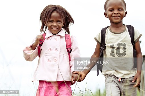 Happy young brother and sister holding hands