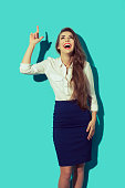 Happt young buisness woman pointing up with finger. Beautiful elegant female smiling. Studio shot on blue background.