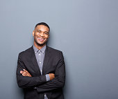 Portrait of a happy young business man smiling with arms crossed on gray background