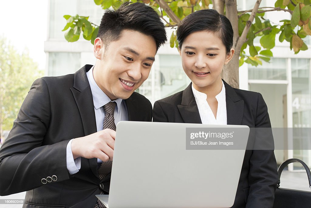 Happy young business partners using laptop outdoors : Stock Photo