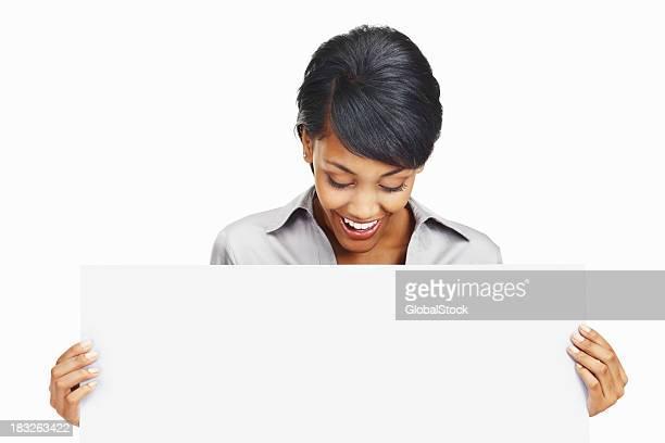 Mujer de negocios joven feliz mirando a placa en blanco