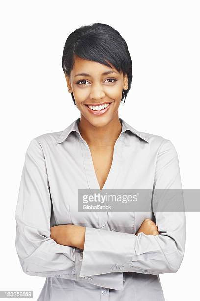 Happy young business woman with hands folded against white