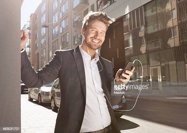 Happy young businessman listening music through mobile phone on street
