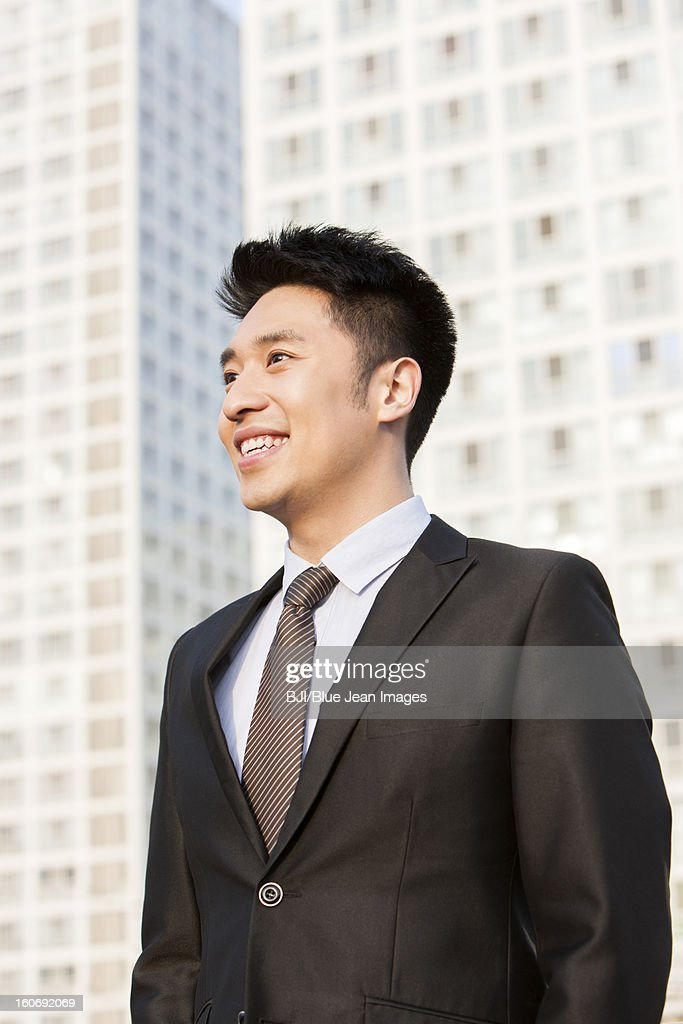 Happy young businessman looking at view in downtown district : Foto de stock