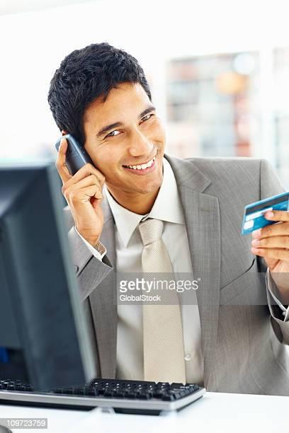 Glückliche junge Geschäftsmann, online-shopping, sprechen auf cellphone