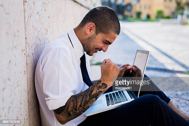 Happy young businessman sitting on the ground looking at his laptop