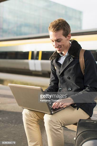 Happy young businessman using laptop on railroad station