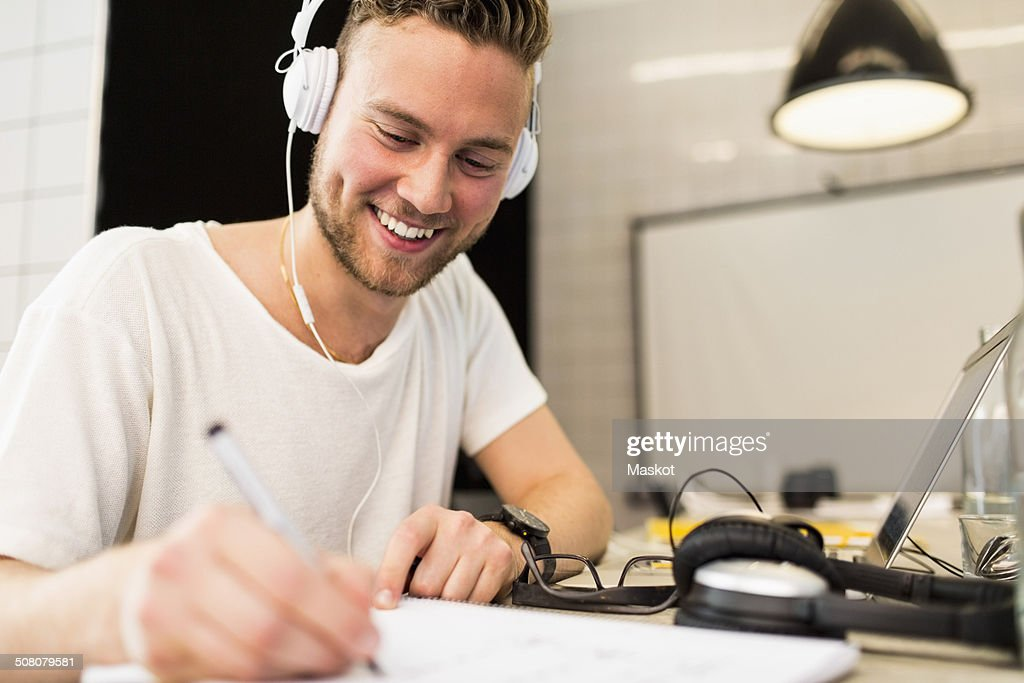 Happy young businessman wearing headphones while writing in book at creative office