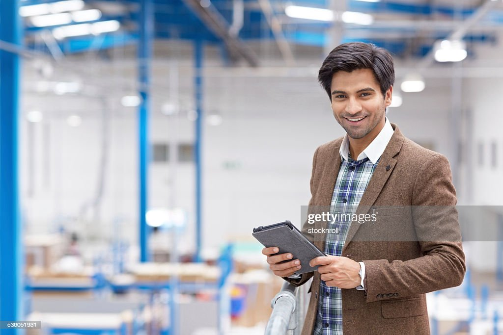 Happy young businessman with digital tablet in warehouse : Stock Photo