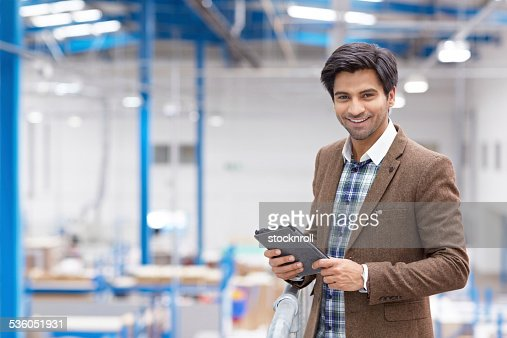 Happy young businessman with digital tablet in warehouse