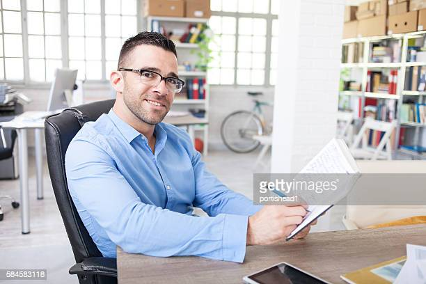 Happy young businessman writing notes