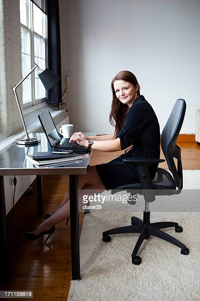 Happy young businesswoman at her desk