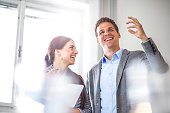 Happy young businesswoman looking at male colleague in office