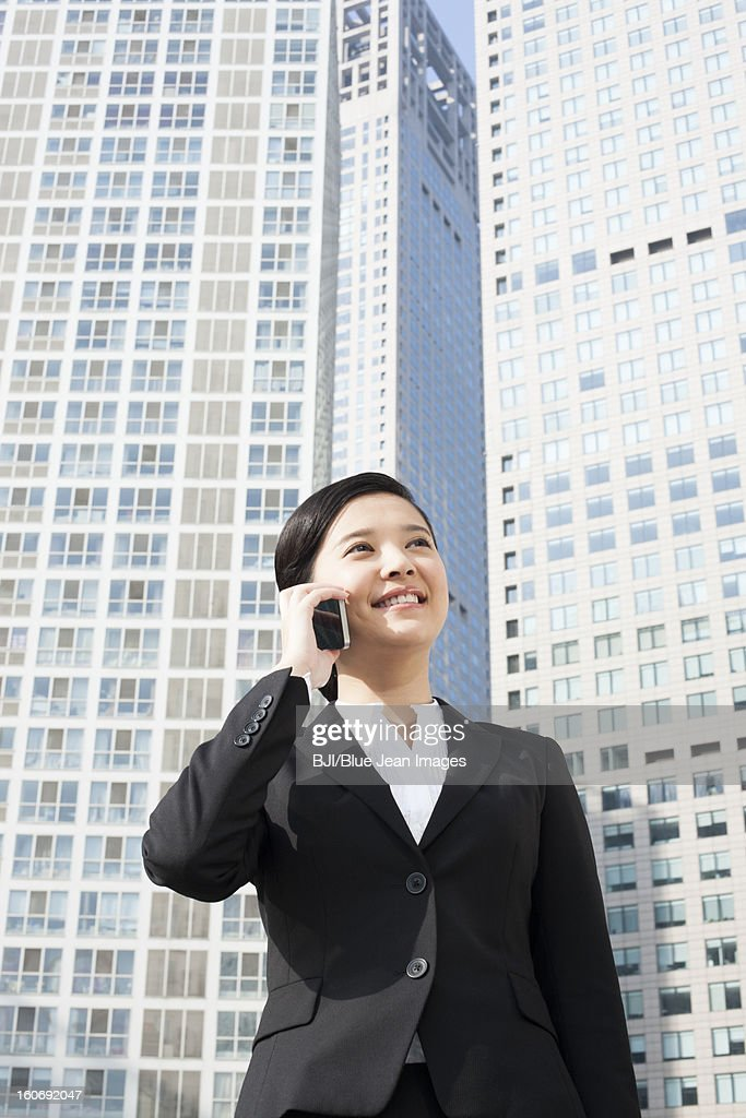 Happy young businesswoman on the phone in front of tall building : Stock Photo